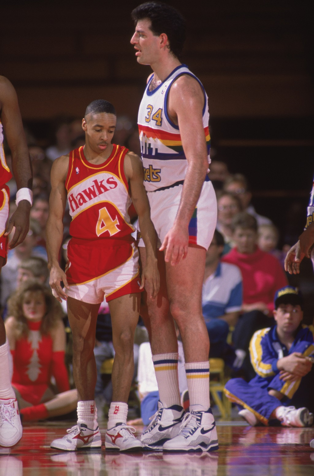 DENVER - 1989: Spud Webb #4 of the Atlanta Hawks tries to maneuver around a much larger opponent during a NBA game at McNichols Sports Arena in Denver, Colorado in 1989.(