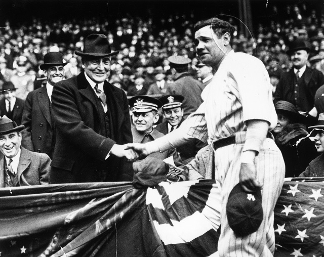 Babe Ruth shakes hands with a fan.
