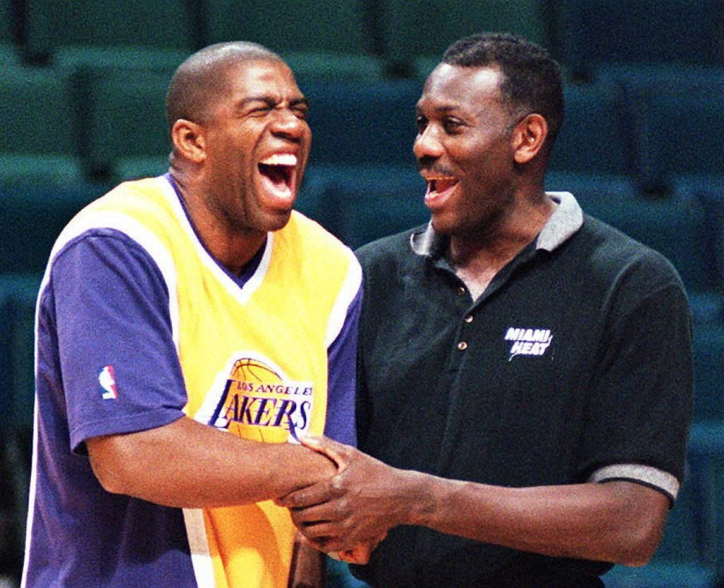 "MIAMI, UNITED STATES: Los Angeles Laker forward Earvin ""Magic"" Johnson shares a pre-game laugh with Miami Heat assistant coach Bob McAdoo before their game 27 March at the Miami Arena. The Lakers won 106-95."