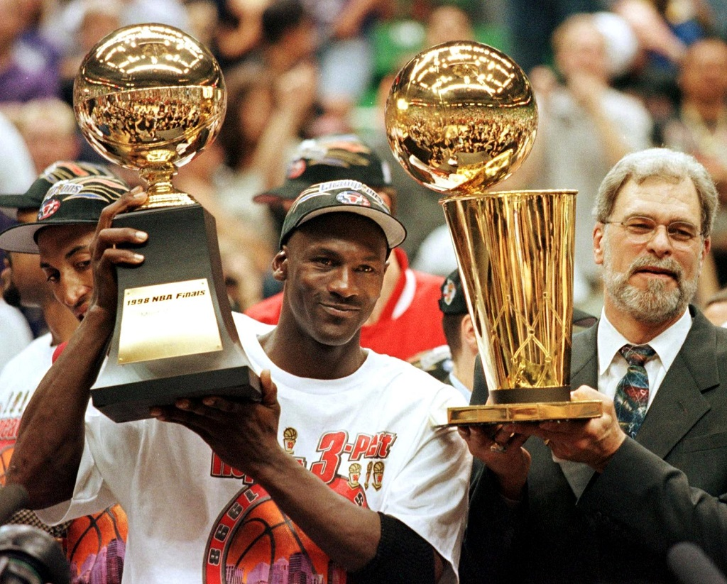 Michael Jordan, the center of one of the most hotly-debated NBA myths, holds up a championship trophy