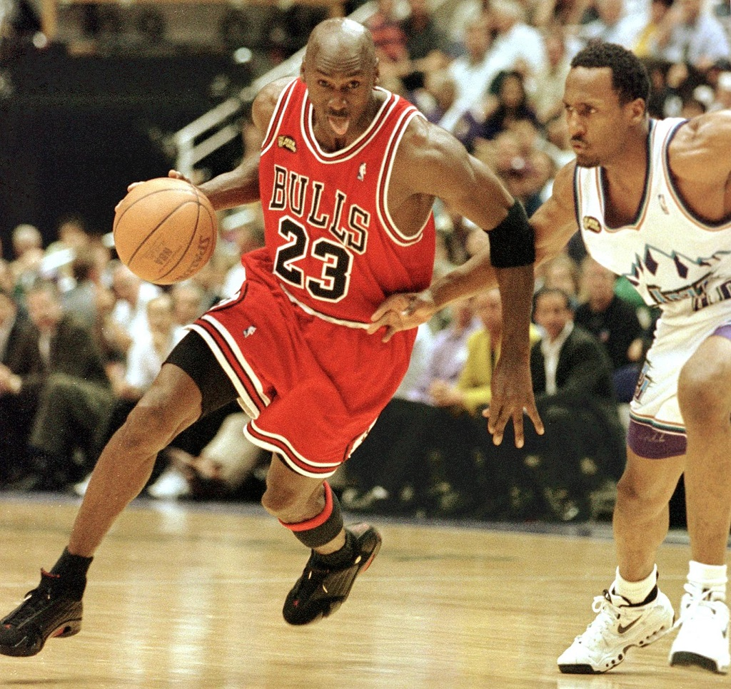Michael Jordan (L) of the Chicago Bulls goes to the basket past Shandon Anderson of the Utah Jazz 14 June during game six of the NBA Finals at the Delta Center in Salt Lake City, UT. The Bulls lead the best-of-seven series 3-2.