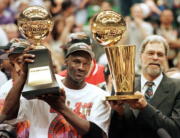 SALT LAKE CITY, UNITED STATES: Michael Jordan (L) and Chicago Bulls head coach Phil Jackson (R) Most Valuable Player trophy (L) and the Larry O'Brian trophy (R) 14 June after winning game six of the NBA Finals with the Utah Jazz at the Delta Center in Salt Lake City, UT. The Bulls won the game 87-86 to take their sixth NBA championship. AFP PHOTO Jeff HAYNES (Photo credit should read JEFF HAYNES/AFP/Getty Images)