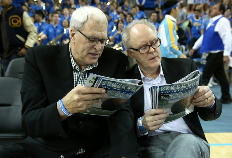 LOS ANGELES, CA - JANUARY 09: NBA coaching legend Phil Jackson (L) and actor John Lithgow consult their programs before the game between the Arizona Wildcats and the UCLA Bruins at Pauley Pavilion on January 9, 2014 in Los Angeles, California. (Photo by Stephen Dunn/Getty Images)
