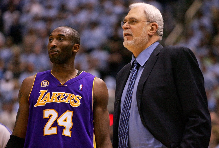 Kobe Bryant and Phil Jackson standing together on the court.
