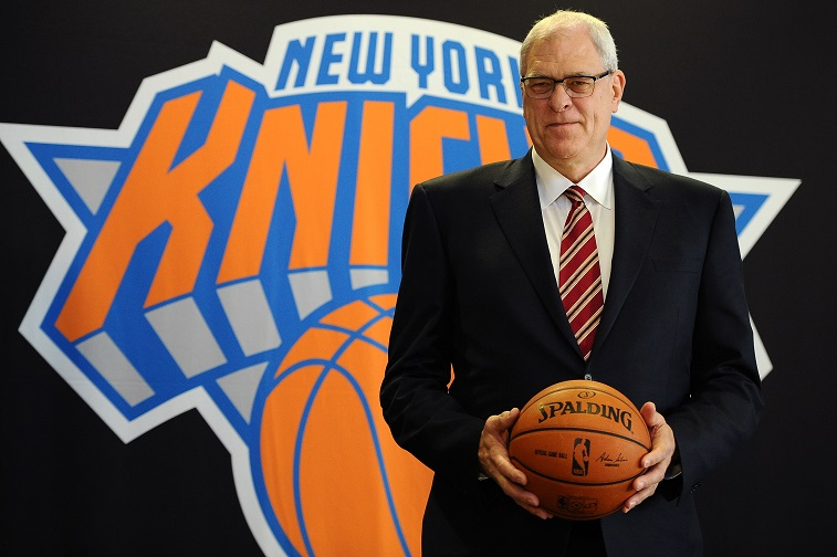 Phil Jackson holding a basketball and posing in front of the New York Knicks logo