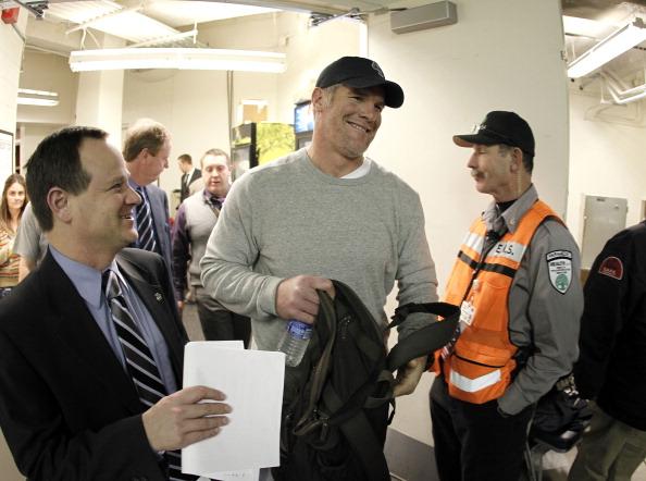 Brett Favre smiles as he walks toward the locker room.