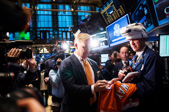 John Elway signs his jersey while visiting the New York Stock Exchange.