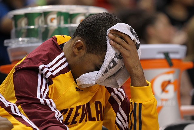 A Cleveland Cavaliers player puts a towel over his head while he sits on the bench.