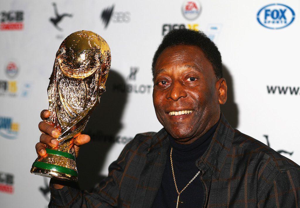 Pele holds a trophy.