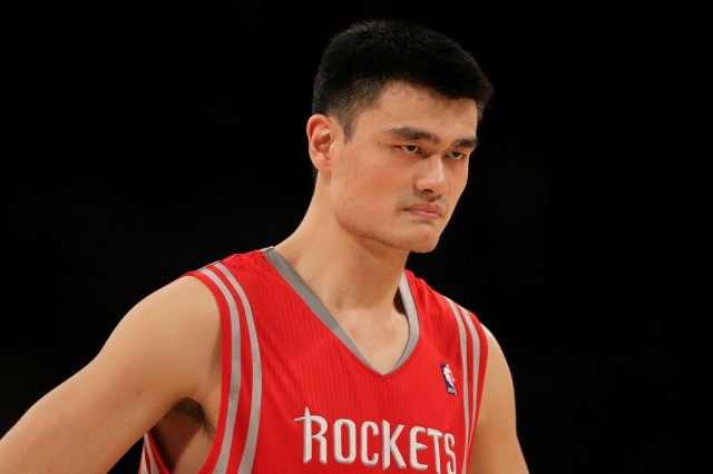 Yao Ming stands on the basketball court between plays.