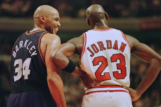 Charles Barkley and Michael Jordan laugh as they stand on the court.