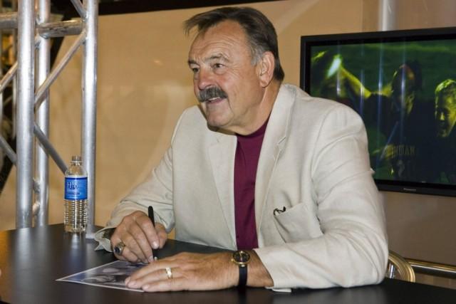 Dick Butkus autographs a photo