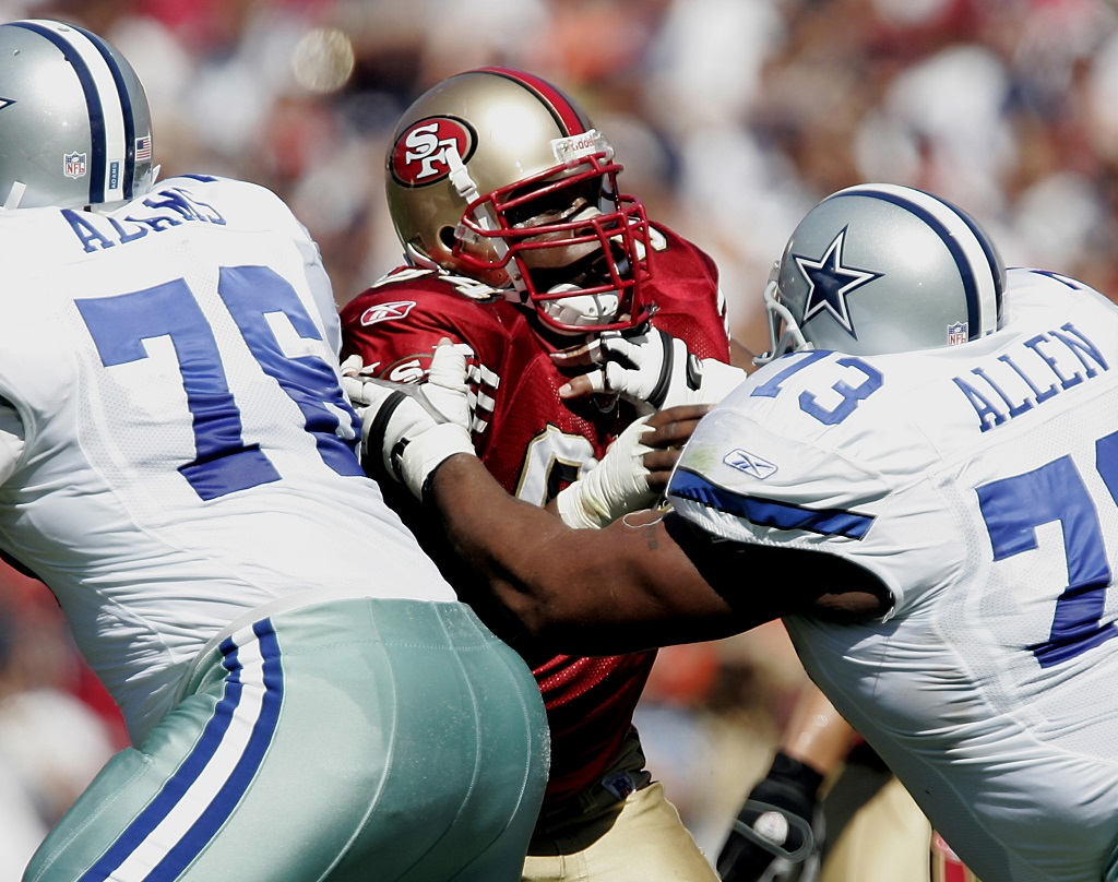 49ers defensive end Marques Douglas is stopped at the line by Dallas guard Larry Allen.