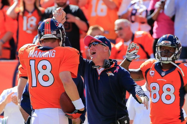 Peyton Manning celebrates with his coach as he walks off the field.