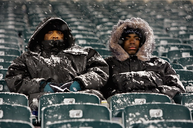 NFL players sitting in the snowy stands