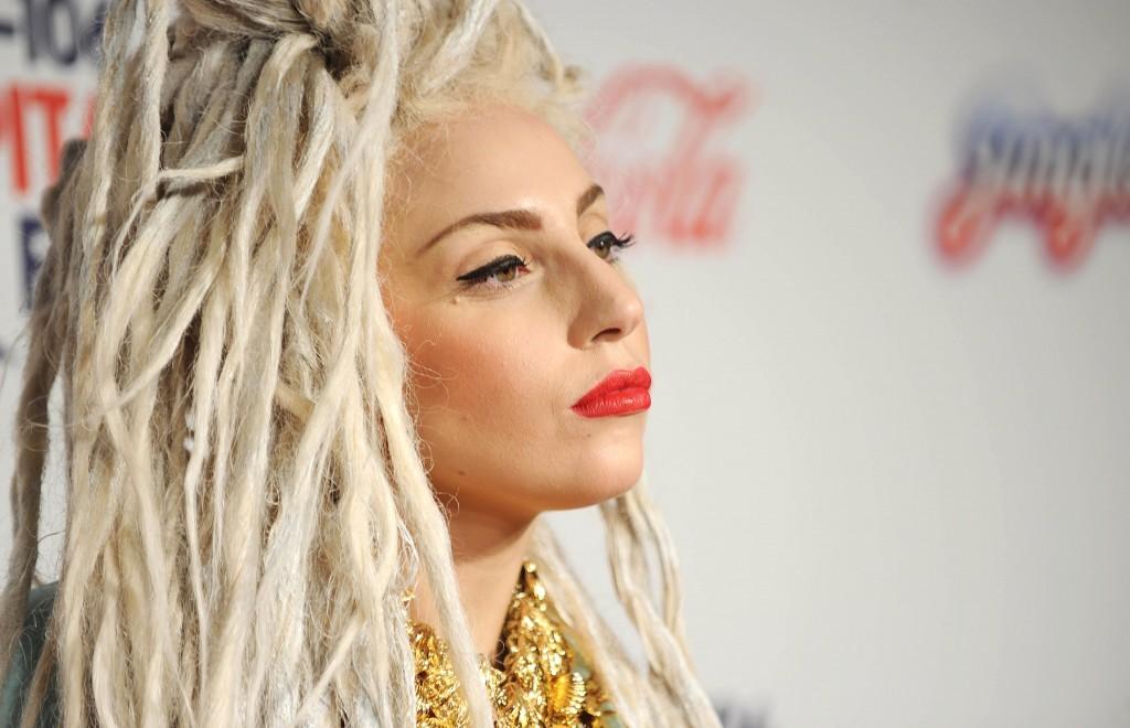 Lady Gaga smiles on the red carpet.