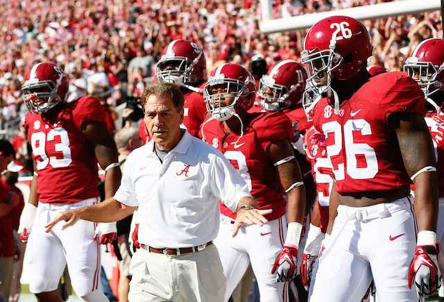 Nick Saban leads Alabama onto the field