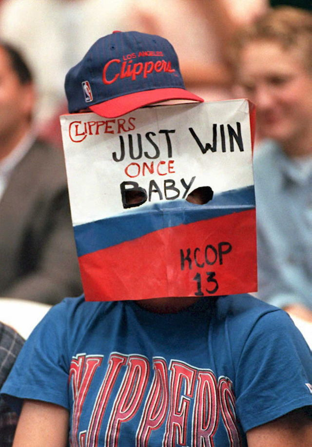 "A Clippers fan wears a sign that reads, ""Just win once, baby."""