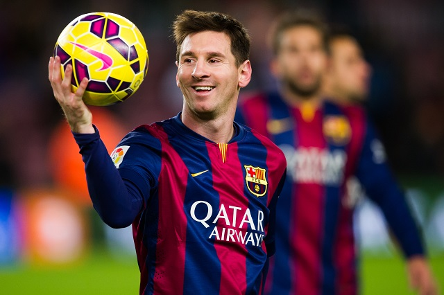 Lionel Messi tosses a soccer ball during warmups.