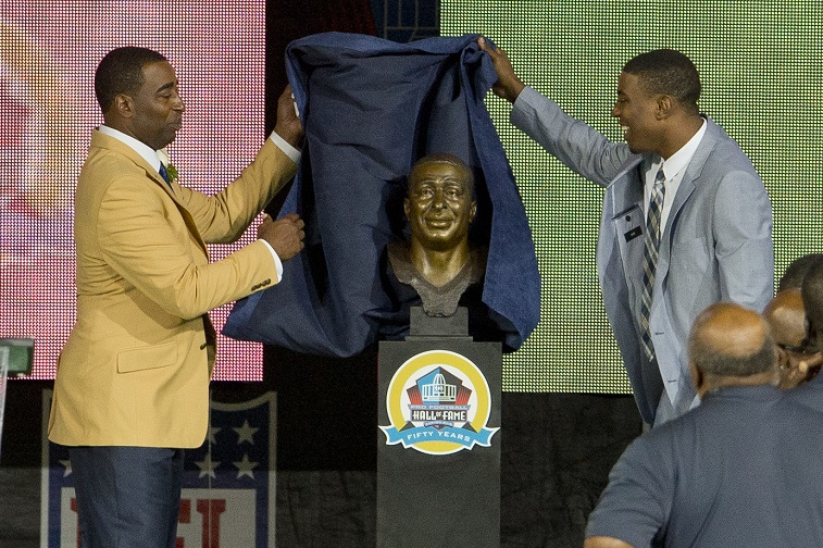 CANTON, OH - AUGUST 3: Duron Carter (R) presents his father and former receiver Cris Carter of the Minnesota Vikings with his Hall of Fame bust during the NFL Class of 2013 Enshrinement Ceremony at Fawcett Stadium on Aug. 3, 2013 in Canton, Ohio. (Photo by Jason Miller/Getty Images)