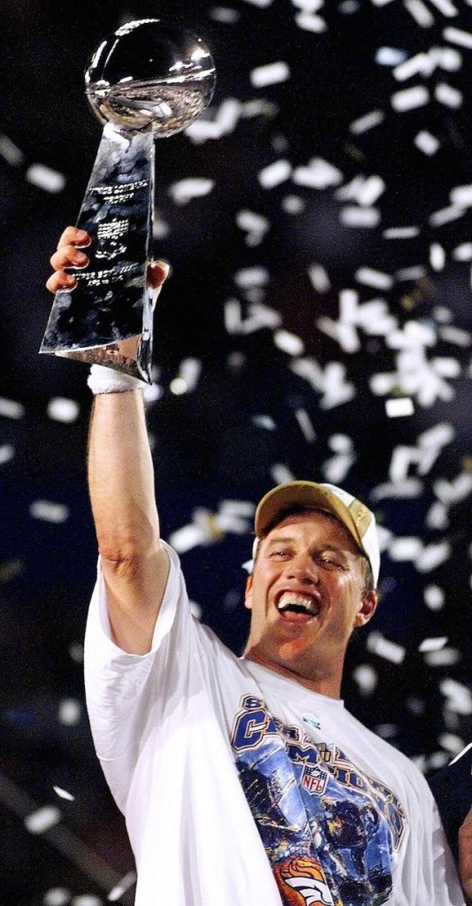 John Elway hoists the Lombardi Trophy after winning the Super Bowl.