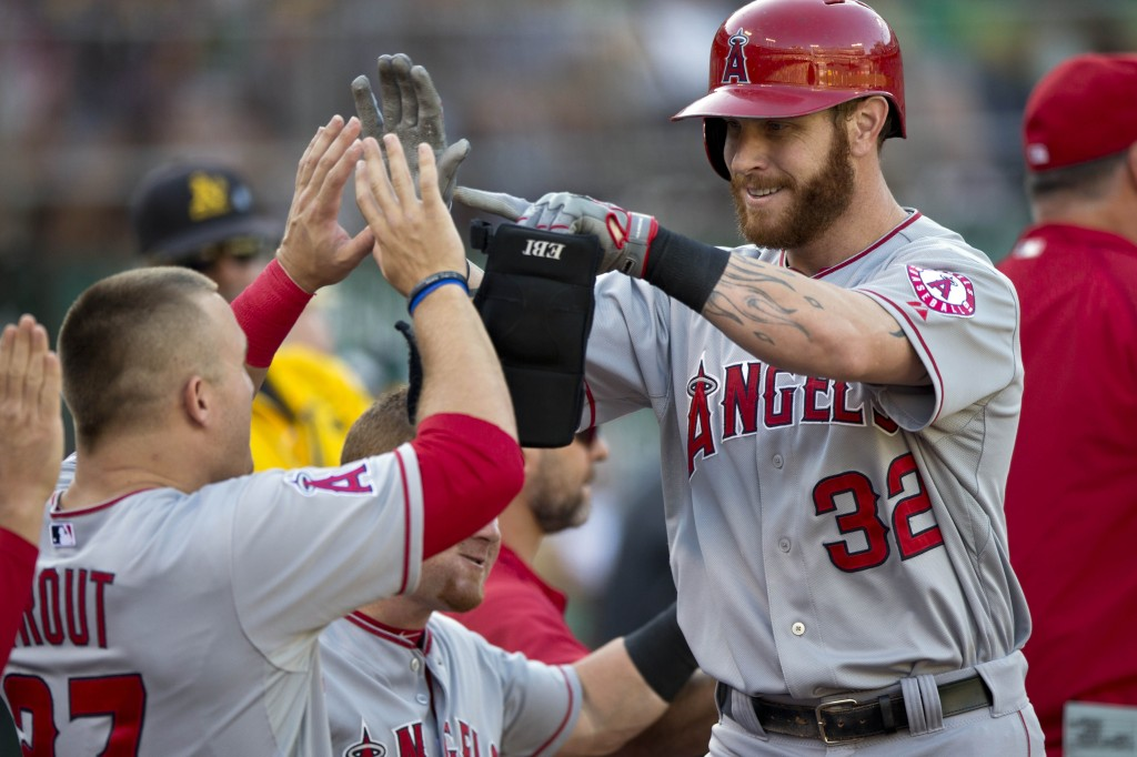 Josh Hamilton of the Los Angeles Angels of Anaheim is congratulated by Mike Trout in the dugout