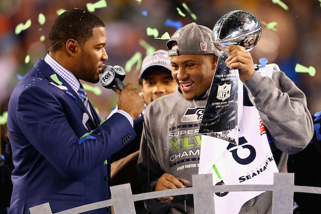 Malcolm Smith holds the MVP trophy for Super Bowl XLVIII.