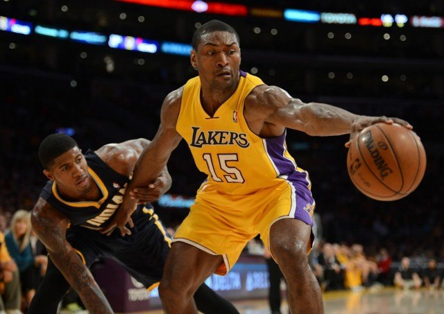 Basketball player Metta World Peace defending the ball from an opposing team member