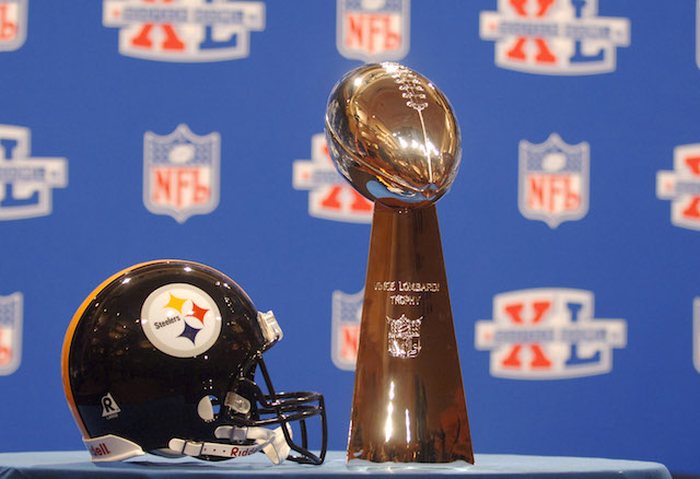 A Pittsburgh Steelers helmet and the Lombardi Trophy rest on a table before a press conference.