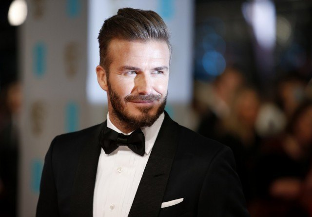 David Beckham smiles as he stands on the red carpet.