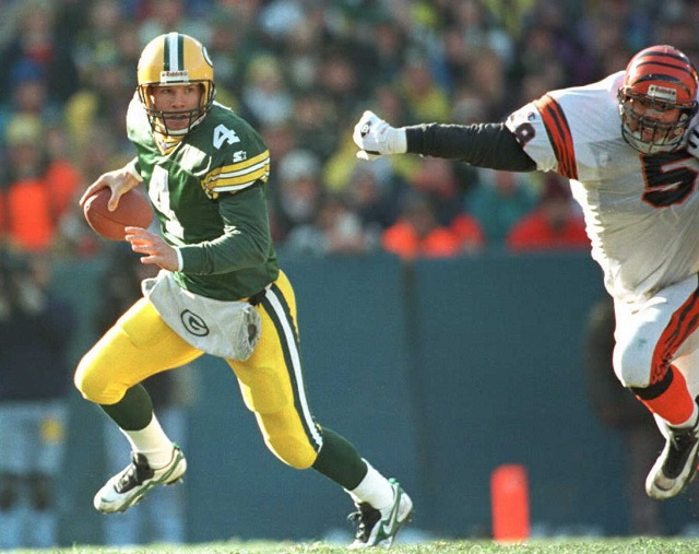 Brett Favre grips the ball and makes a run for it.