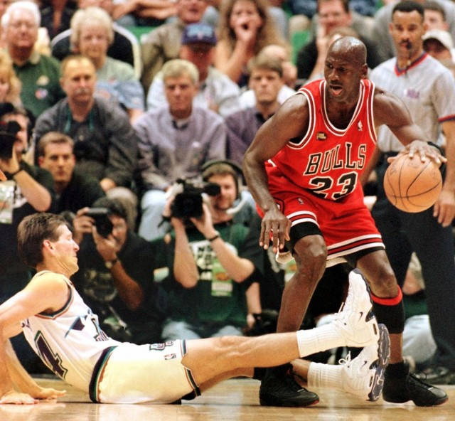 Michael Jordan tries to drive the ball past an opponent who has fallen to the ground.