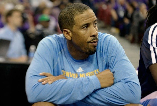 Andre Miller watches from the bench.