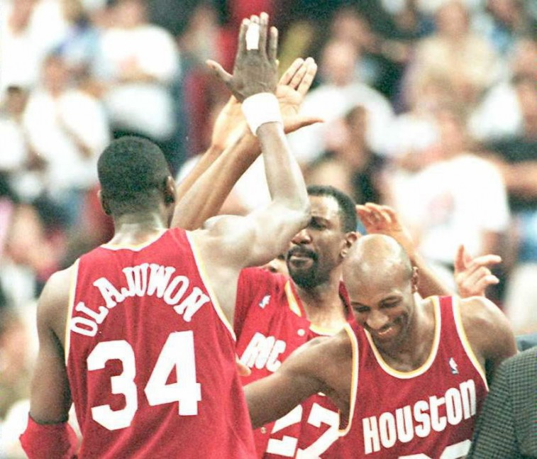 Members of the Houston Rockets high five each other and celebrate a victory.