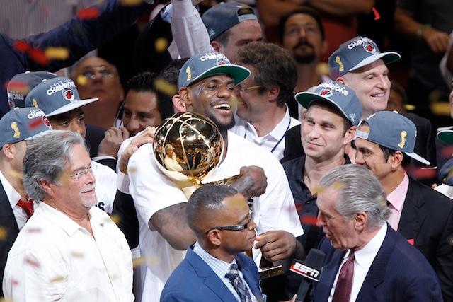 LeBron James hugs the Larry O'Brien Trophy after winning an NBA championship with the Miami Heat.