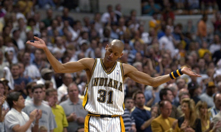 Reggie Miller lifts his arms in the air and cheers.