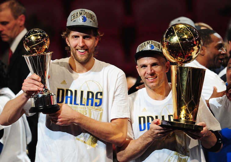 Members of the Dallas Mavericks hold up their championship trophies.