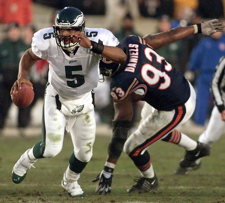 CHICAGO, UNITED STATES:  Philadelphia Eagles quarterback Donovan McNabb (L) scrambles away from Phillip Daniels (R) of the Chicago Bears before throwing for a touchdown pass at the end of the second quarter during their NFC Divisional Playoff game 19 January 2002, at Soldier Field in Chicago, IL.