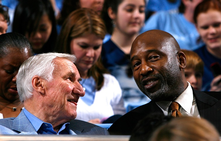 Dean Smith (L) and James Worthy (R) converse before the game.