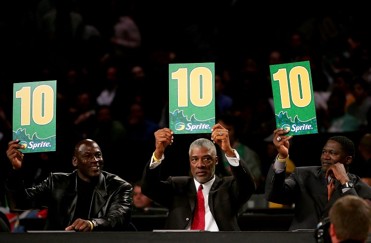 Michael Jordan (L) and Dominique Wilkins (C) hold up signs as they judge the Slam Dunk Contest.