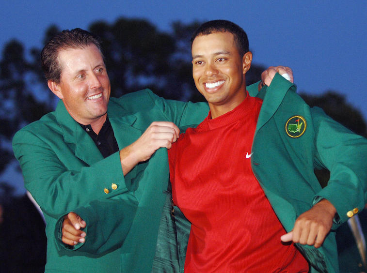 Phil Mickelson puts the Masters' green jacket on Tiger Woods.