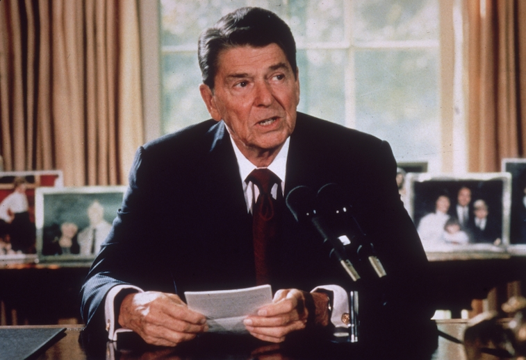 Ronald Reagan sits in the Oval Office of the White House.