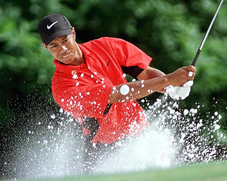 Tiger Woods chips out of the bunker on the fifth green during the Masters tournament.