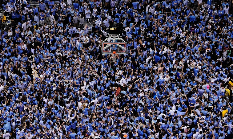 Tar Heels fans cheer at a basketball game.