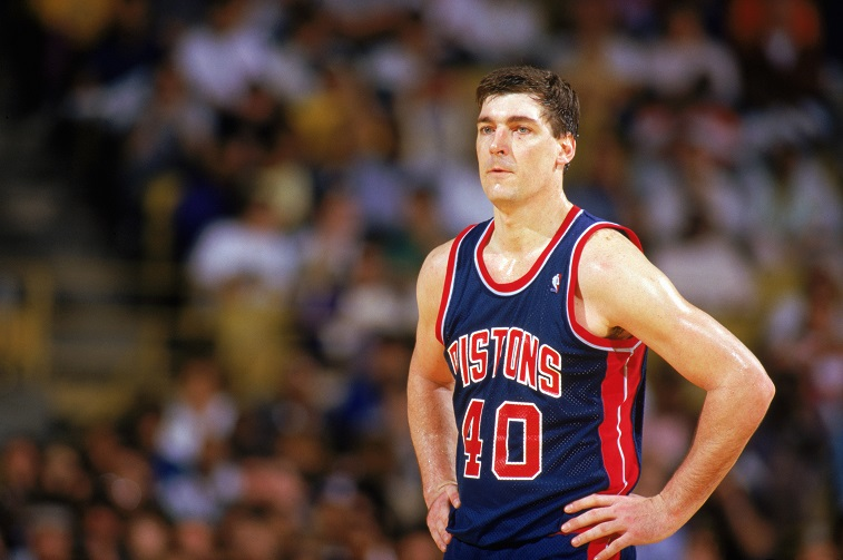 Bill Laimbeer stands on the court with his hands on his hips.