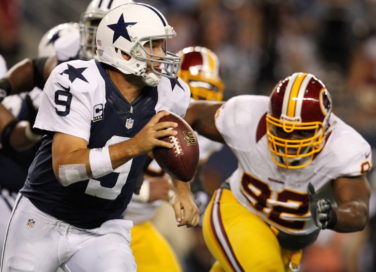 ARLINGTON, TX - NOVEMBER 22: Tony Romo #9 of the Dallas Cowboys looks for an open receiver under pressure from Chris Baker #92 of the Washington Redskins on Thanksgiving Day at Cowboys Stadium on November 22, 2012 in Arlington, Texas. The Washington Redskins beat the Dallas Cowboys 38-31. (Photo by Tom Pennington/Getty Images)