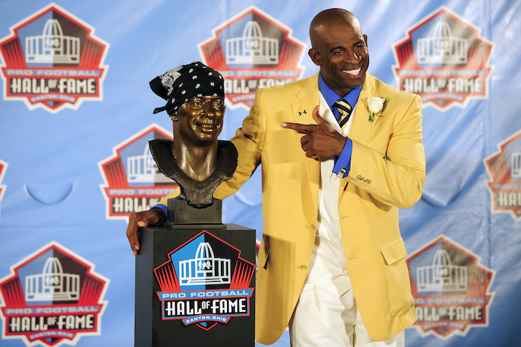 Deion Sanders smiles next to his Hall of Fame bust.