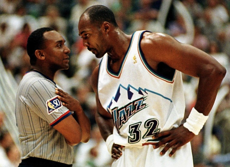 Karl Malone puts his hands on his hips and looks down at the referee.