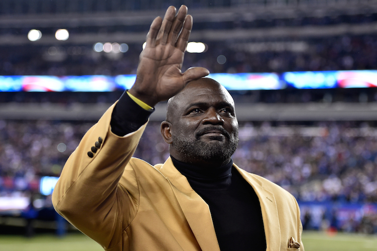 Lawrence Taylor waves at fans before a game.