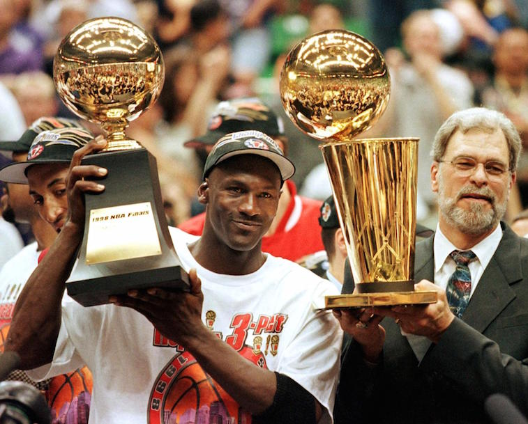 Michael Jordan and Phil Jackson hold the trophies.